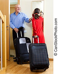 Happy mature couple with suitcases looking in mirror near...