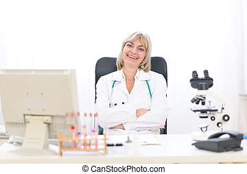 Happy mature doctor woman at office