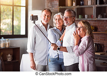 Happy mature family taking selfies with smartphone in the kitchen