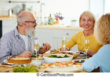 Happy mature friends having dinner together