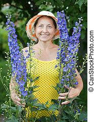 gardener in delphinium plant - Happy mature gardener in ...