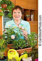 Happy mature gardener with flowers smiling
