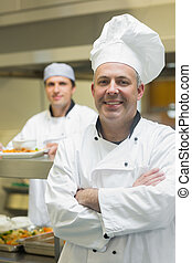 Happy mature head chef posing with crossed arms