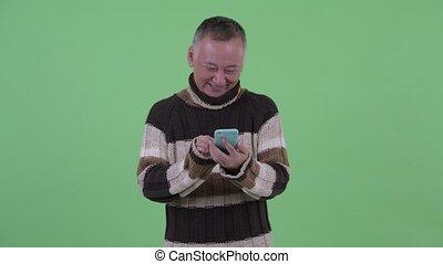 Happy mature Japanese man thinking while using phone