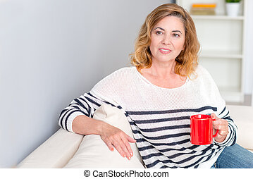 Happy mature lady enjoying hot drink