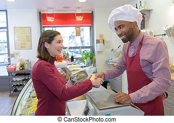 happy mature male butcher selling fresh meat to female customer