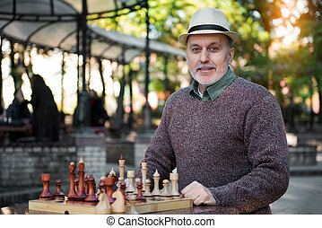 Happy mature male pensioner relaxing near chessboard in park