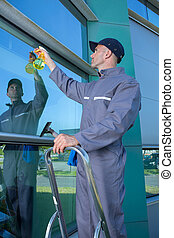 happy mature male worker cleaning glass