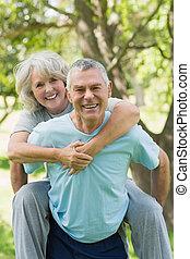 Happy mature man carrying woman at park
