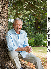 Happy mature man sitting on tree trunk looking at camera in...