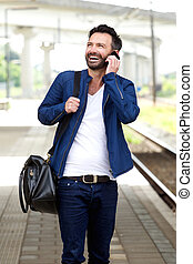 Happy mature man using mobile phone on train station