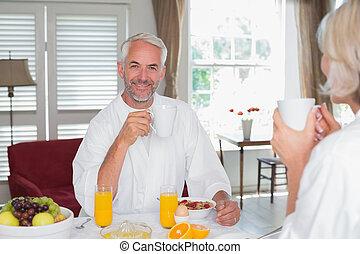 Happy mature man with woman having breakfast