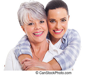 happy mature mother and adult daughter hugging on white...