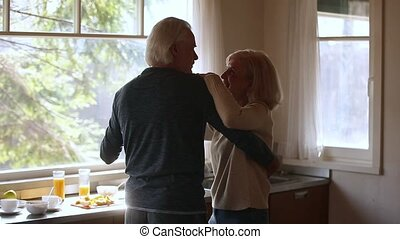 Happy mature senior couple dancing laughing in the kitchen,...