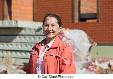 Happy mature woman against building residence