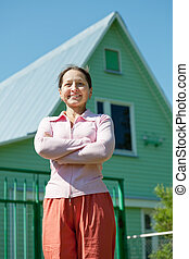 Happy mature woman against her  home