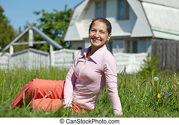 Happy mature woman against  residence