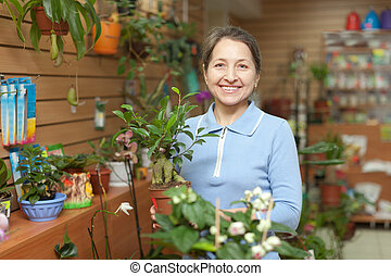 mature woman chooses Bonsai - Happy mature woman chooses...