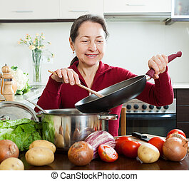 Happy mature woman cooking lent diet lunch