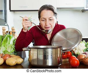 Happy mature woman cooking lent diet soup in  kitchen