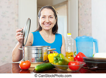 Happy mature woman cooking lunch