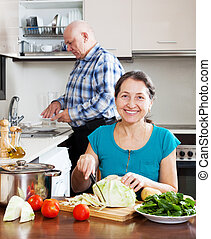 mature woman cooking with husband