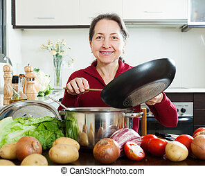 Happy mature woman cooking  with skillet