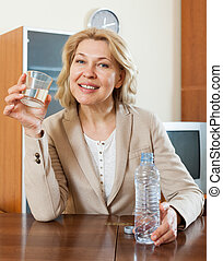 Happy mature woman drinking water