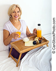 Happy mature woman enjoying  breakfast