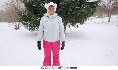 Happy mature woman falling down in snowdrift enjoying...