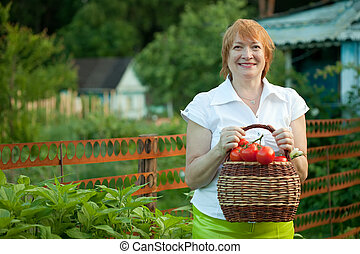 Happy mature woman  harvested vegetables