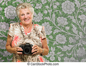 Happy Mature Woman Holding Camera, Indoors