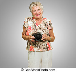 Happy Mature Woman Holding Camera On Grey Background