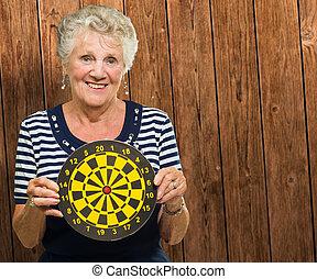 Happy Mature Woman Holding Dart Board