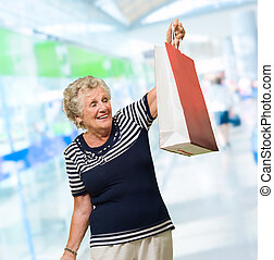 Happy Mature Woman Holding Shopping Bag, Indoors