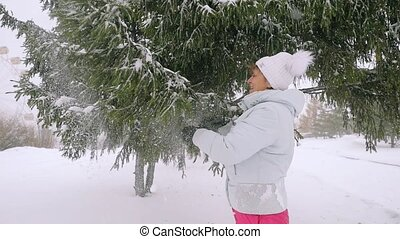 Happy mature woman in aged shaking snowy branches in slowmotion. 1920x1080