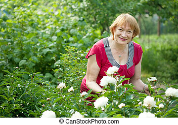 Happy mature woman in  peony plant
