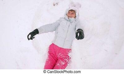 Happy mature woman in winter wear lying in snowdrift enjoying snowfall in slowmotion. 1920x1080