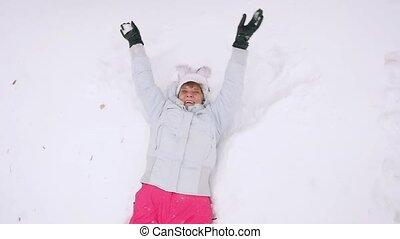 Happy mature woman in winter wear lying in snowdrift...