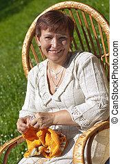 Happy mature woman knitting in garden