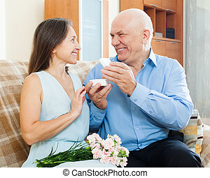 Happy mature woman looking jewel from man