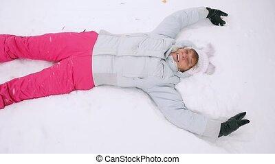 Happy mature woman lying in snowdrift enjoying snowfall in...