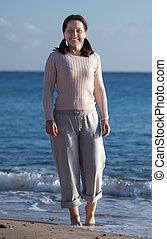 Happy mature woman on  beach