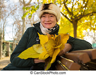 Happy mature woman on bench in autumn park