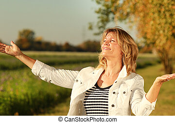 Happy mature woman open her arms while enjoying the sunbeams