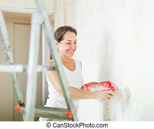 Happy mature woman paints wall with brush at home