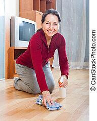Happy mature woman rubbing wooden floor
