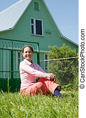 Happy mature woman sitting on lawn