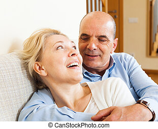 Happy mature woman smiling and hug with husband in home...