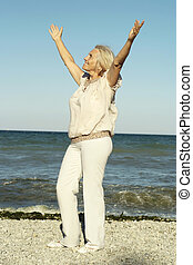 Happy mature woman relaxing on the beach